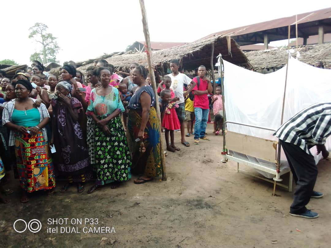 Community members wait to receive nets, next to an example of a hung net